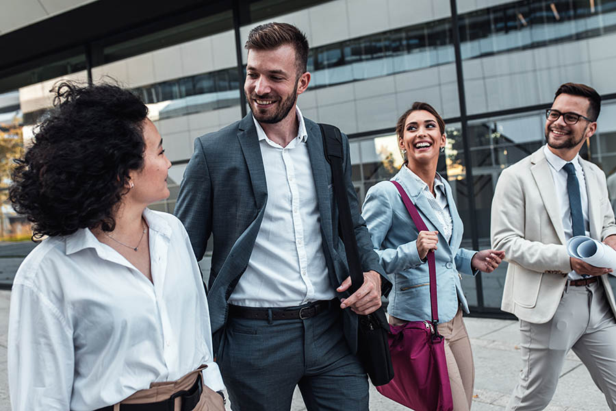 About Us - Group of Four Professionally Dressed Coworkers Strolling City Street Smiling and Talking With Glass Building Behind Them
