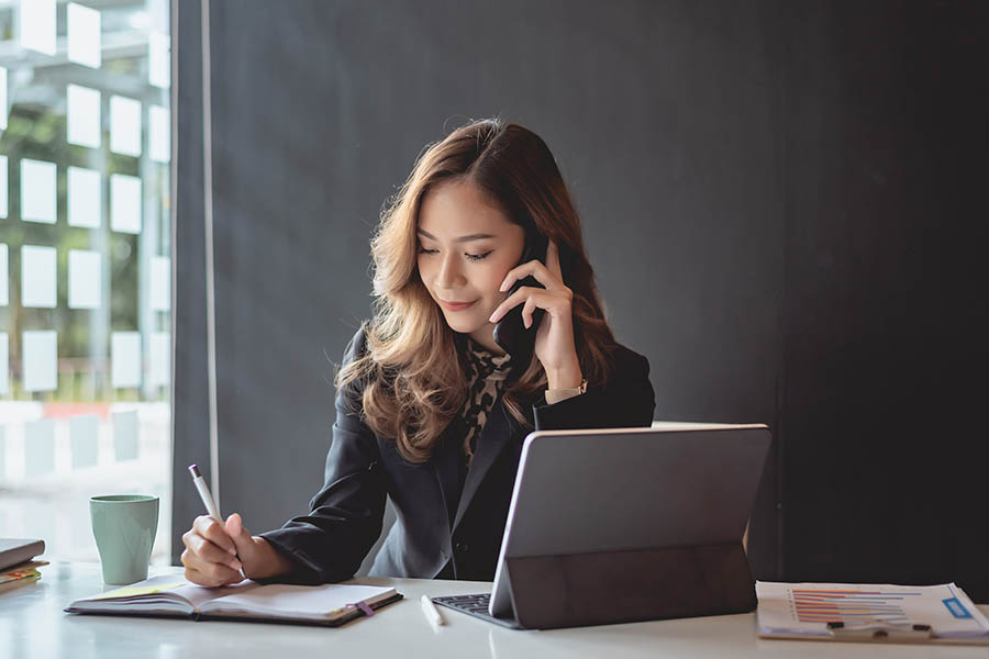 Contact Us - Businesswoman Takes Notes in a Notebook While Making a Phone Call at Her Desk in a Concrete and Glass Office