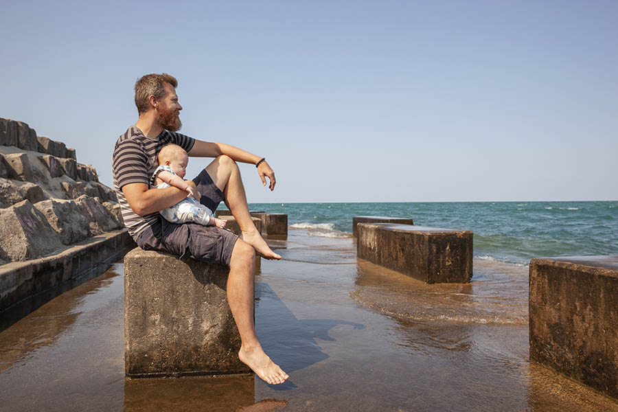 Personal Insurance - Father Holding His Baby on a Concrete Bench Overlooking Lake Michigan at Promontory Point in Chicago